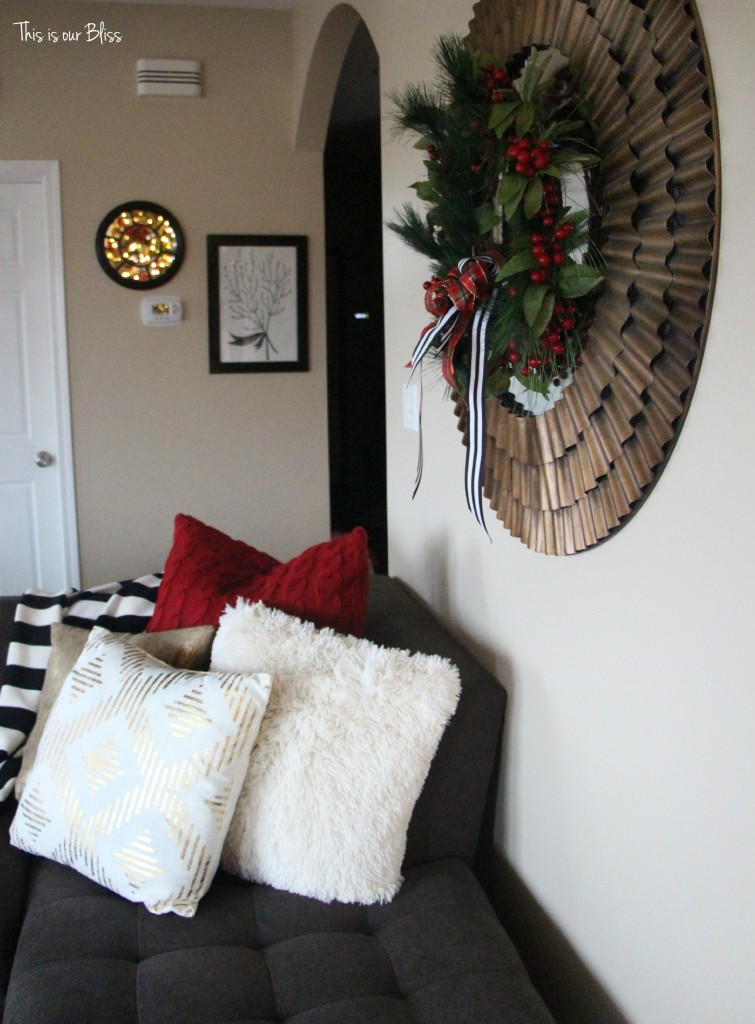 family room couch with holiday pillows - sunburst mirror with wreath - This is our bliss