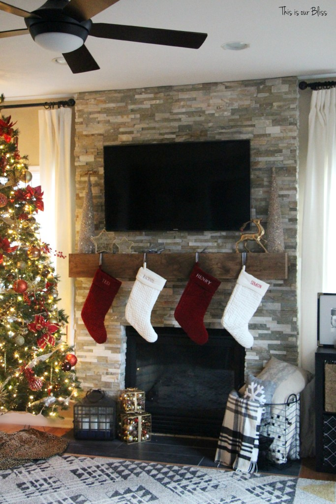 family room tree - stockings hung on mantle - stacked stone fireplace - floating mantle - This is our Bliss