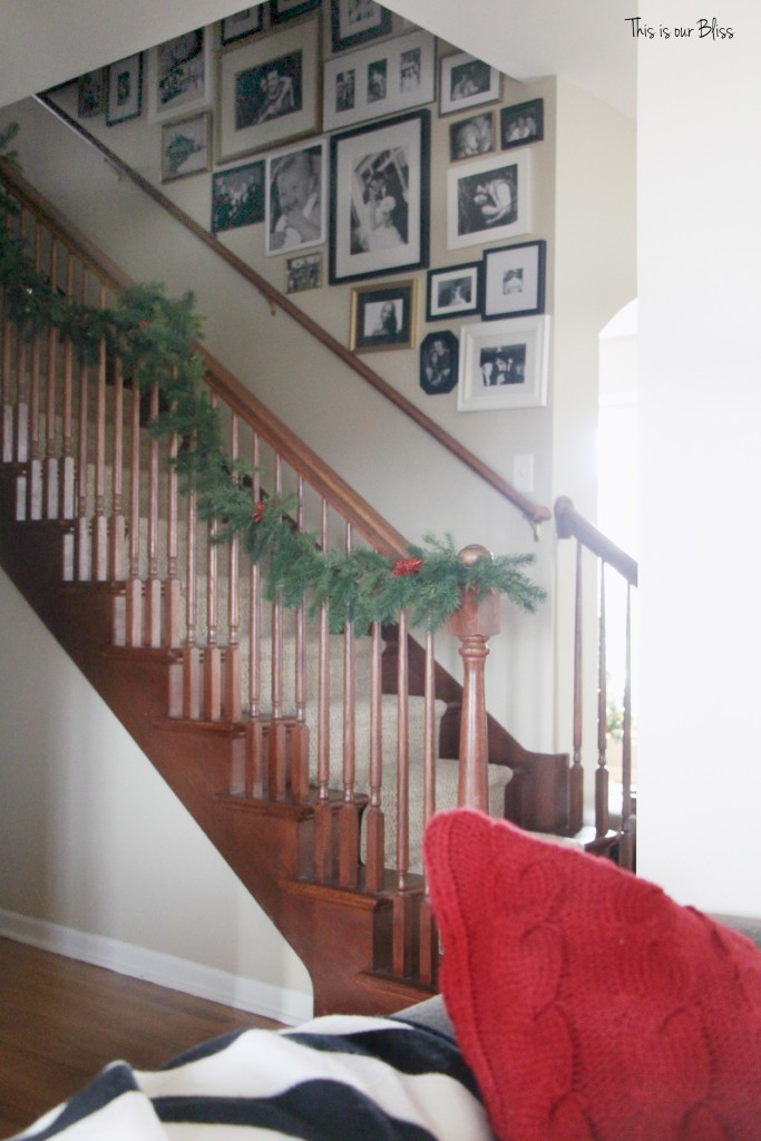 merry bright and blissful holiday home - stairwell gallery wall - staircase garland - thisisourbliss.com
