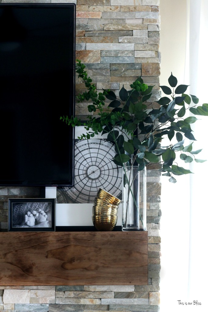 How to style a mantle - black white and gold display w pops of green on rustic floating mantle - stacked stone This is our Bliss www.thisisourbliss.com