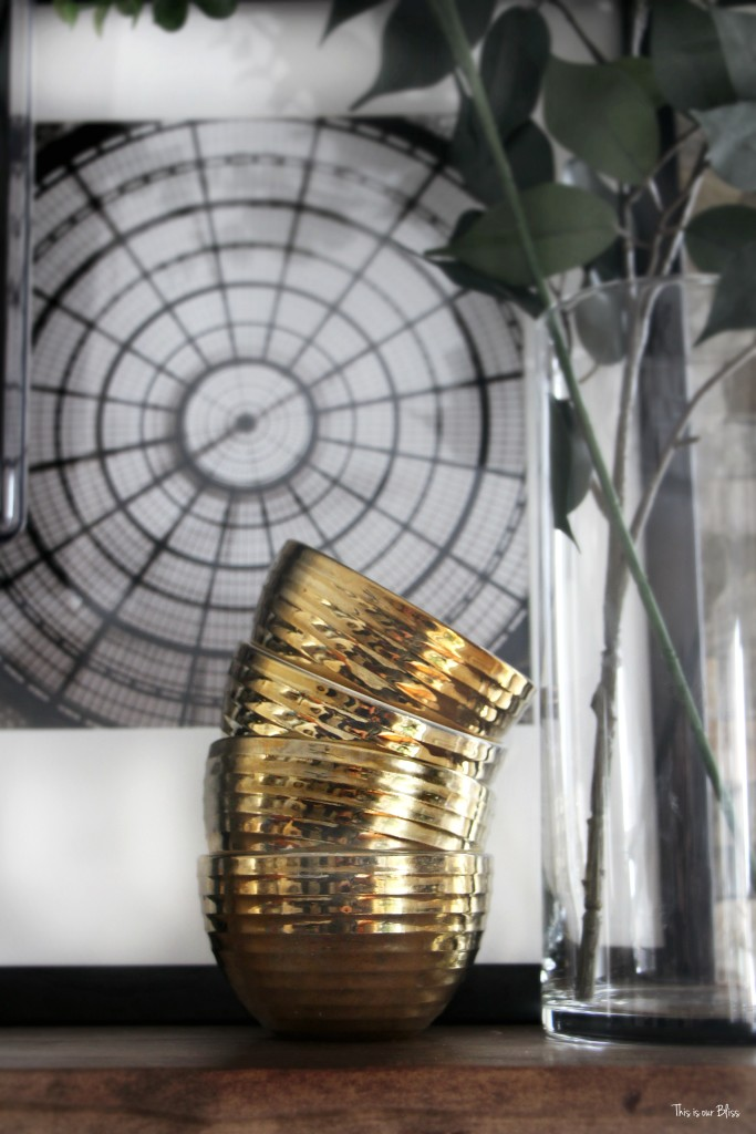 How to style a mantle table top styling hop family room mantle styling stacked gold dishes interesting shape and object This is our Bliss www.thisisourbliss.com